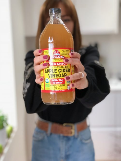Woman Holding Bragg Apple Cider Vinegar In Air