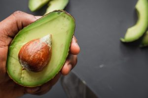 hand holding sliced open avocado